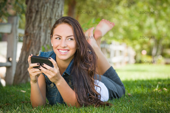 Attractive Happy Mixed Race Young Female Texting on Her Cell Phone Outside Laying in the Grass
