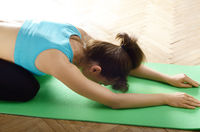 Female model doing yoga stretch relaxing exercise standing on knees on green mat. Healthy lifestyle concept. Place for text