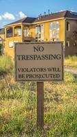 Vertical Close up of No Trespassing sign post beside a paved road that leads to houses