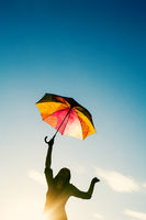 Hppy Woman Dancing With Umbrella In Her Hand In Front Of Clear Sky