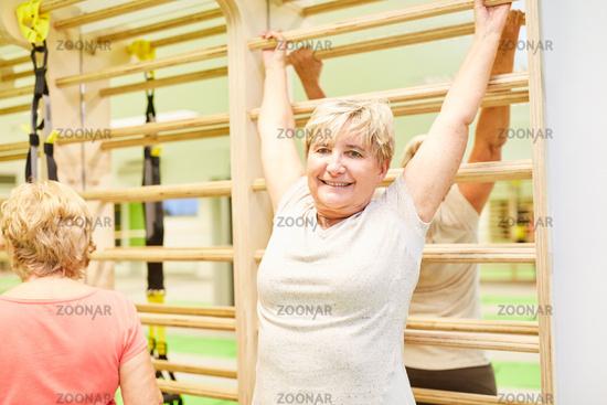 Seniorin macht Rückenübung an der Sprossenwand