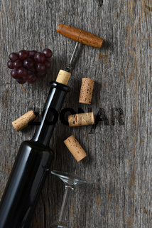Wine bottle on rustic wood tabnle with the cork pulled partially out, with grapes and corks