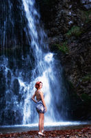 Red-haired woman in front of a waterfall