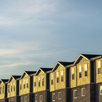 Square frame Townhouses on a neighborhood under blue sky and clouds on a sunny day