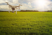 multicopter drone flying over crops field