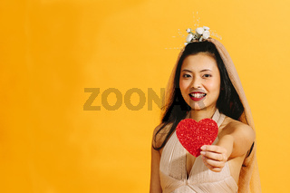 Asian bride in beige wedding dress holding a red heart isolated on orange background