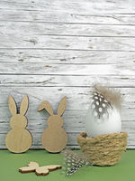 Easter background with Easter egg, Easter bunnies and butterfly isolated on green in front of wood