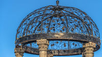 Panorama Cast iron gazebo with dome roof supported by five white stone pillars