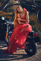 Blond woman wearing red fluffy dress sitting on motorcycle outdoors posing on nature looking at camera