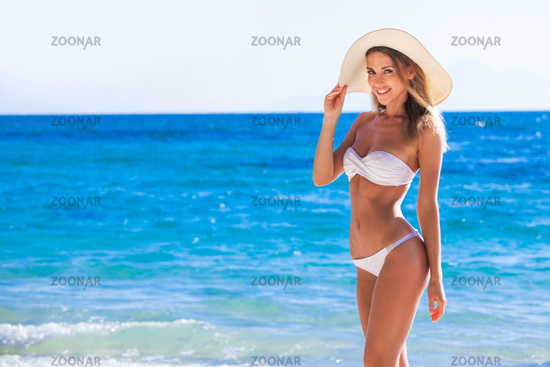 Smiling woman in sunhat on sea beach