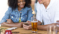 couple with smartphone and beer at bar