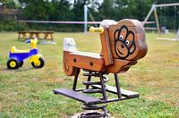 A close-up view of wooden swing on spring with plastic tricycle in the empty playground.