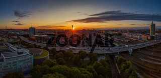 Munich from above at a beautiful sunrise. The red sun next to the famous Frauenkirche by the view from the Donnersberger Br cke with traffic made by drone.