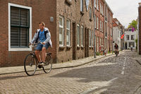 People using bicycles as a traditional way of transportation through streets of town of Vlissingen in Netherlands