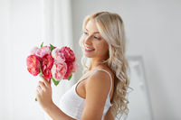 woman in underwear with bunch of flowers at window