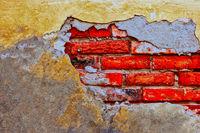 Damaged brick wall with worn plaster