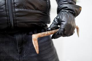 Hand von Einbrecher mit Brecheisen