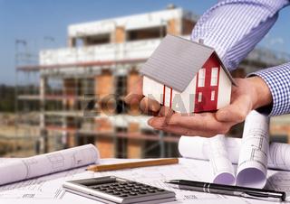 Baustelle mit Rohbau, Architekturmodell und Bauplänen
