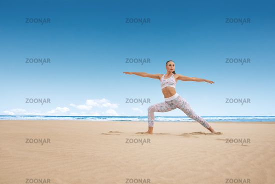 Young woman practice yoga posture warrior pose virabhadrasana at sunny day on the sea beach sand next to water