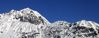 Snowy mountains and blue clear sky at cold sun day