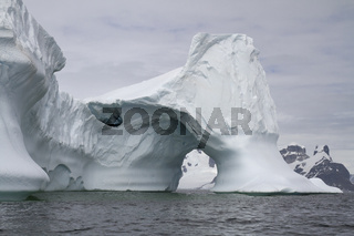 iceberg with an arch in Antarctic waters against the backdrop of the mountains of the Antarctic Peninsula on a cloudy day