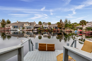 Looking out of Luxurious Wooden Porch Beach Chairs onto Lake Neighborhood Daytime Sunny Weather Architectural