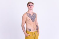 Young happy shirtless man with tattoos smiling