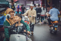 Muslim woman with her son on a scooter