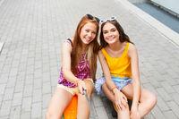 teenage girls taking selfie on city street