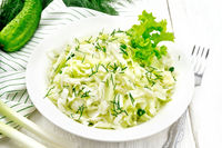 Salad of cabbage and cucumber in plate on white board