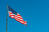 Floating american flag against blue sky