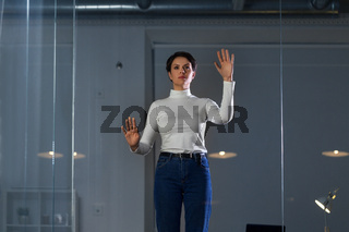 businesswoman using glass wall at night office