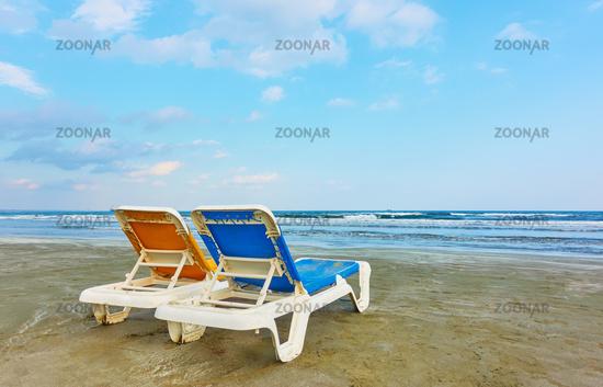 Deckchairs on a sandy beach