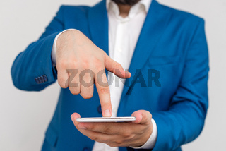Businessman in the blue suite with lap top pointing with finger. Business concept with businessman in the blue suite.
