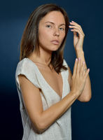 Beautiful  woman in a white dress posing in studio