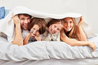 Eltern und Kinder verstecken sich unter Bettdecke