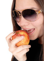 Close up of girl eating a red apple with sunglasses