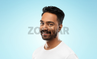 smiling young indian man over blue background