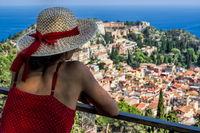 Frau mit Sonnenhut blickt auf Taormina, Sizilien