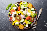 Top view at Mediterranean diet dish greek salad on slate tray