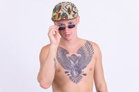 Young handsome shirtless man with tattoos peeking over sunglasses
