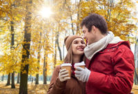 happy couple with coffee walking in autumn park