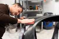 Car mechanic grinds a car part in handicraft in a service station - Serie car repair workshop