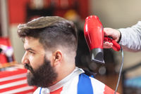 Close up view of master barber doing hairstyle with hairdryer at barber shop.