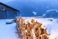 Firewood near a barn in the light