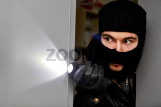 Einbrecher im Haus mit Taschenlampe