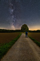 The milkyway watched by a man with a bicycle in foreground.