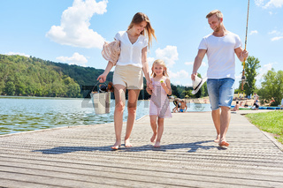 Familie mit Tochter beim Spaziergang am See
