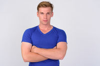 Young handsome blonde man with arms crossed