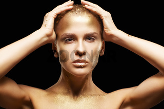 Female with   hands near face. Golden girl on black background
